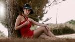 Обои Симпатичная девушка в шляпе и в красном платье позирует сидя на траве, прислонившись к дереву на размытом фоне природы