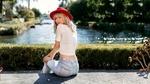 Обои Симпатичная блондинка в шляпке, футболке и в джинсах позирует, сидя на скамейке на фоне водоема и природы