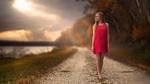 Обои Девушка в ярком красном платье позирует, стоя на проселочной дороге, на размытом фоне природы