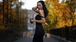 Обои Стройная длинноволосая брюнетка в черном платье позирует, стоя на фоне зданий и деревьев, держа в руке стаканчик с напитком