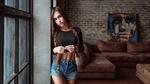 Обои Симпатичная брюнетка с косичками, в короткой кофкочке и в джинсовых шортах позирует, стоя у окна в комнате. Фотограф Георгий Чернядьев