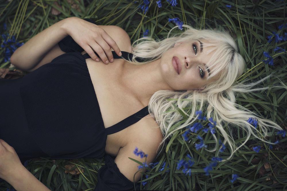 Обои для рабочего стола Девушка-блондинка лежит на траве с голубыми цветами, фотограф Anastasia Vervueren