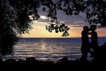 Обои Целующаяся среди деревьев парочка, на фоне закатного моря, by Ms. Kathrynne