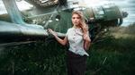 Обои Симпатичная блондинка в светлой блузке в горошек позирует, стоя у самолета в поле с травой, фотограф Кузин Макс