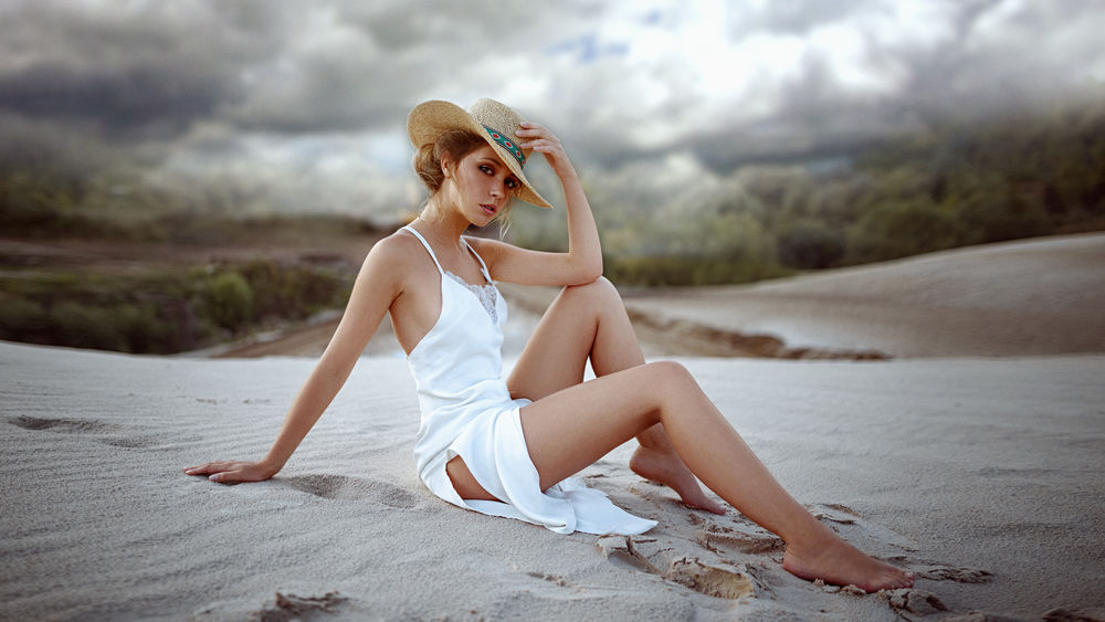 Обои для рабочего стола Модель Ксения в шляпе и белом платье сидит на песке, фотограф Георгий Чернядьев