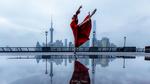 Обои Балерина в красном платье стоит на фоне города