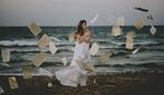 Обои Девушка в белом платье стоит у моря в окружении парящих в воздухе страниц. Фотограф Vicente Serra