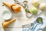 Обои Шарики ванильного и фисташкового мороженого, вафельные рожки и ложки лежат на деревянной поверхности
