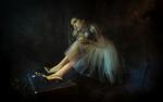 Обои Девочка в золотых туфельках и балетном платье сидит в темной комнате, обнимая мишку-Тедди фотограф Galeg