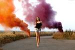 Обои Девушка идет по асфальтированной дороге на фоне дымящих шашек с разноцветным дымом, фотограф Александр Исаев