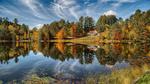 Обои Небольшой коттедж на берегу озера окружен осенними деревьями. Фотограф Jens Bernard
