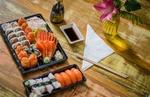 Обои Японская кухня: два блюда с ассорти из суши и роллов рядом палочки для еды соус и вазочка с цветком