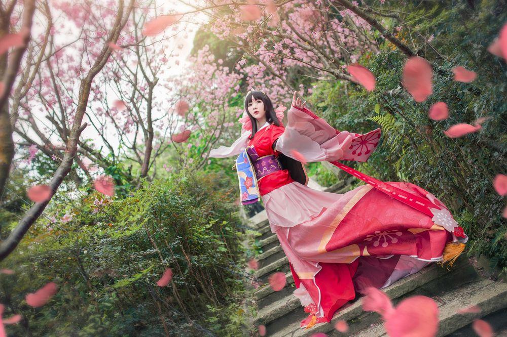 Обои для рабочего стола Девушка-азиатка стоит на лестнице в цветущем саду