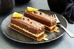 Обои Шоколадные пирожные-полоски с кремом, глазурью и кусочками апельсина на черной тарелке, рядом вилка