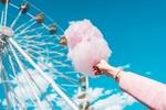 Обои Женская рука с розовой сахарной ватой на фоне голубого неба и колеса обозрения
