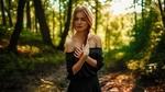 Обои Симпатичная девушка в приспущенном с плеч черном платье позирует, стоя в лесу