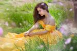 Обои Девушка в желтом платье задумалась, сидя на траве, фотограф Malika Drobot