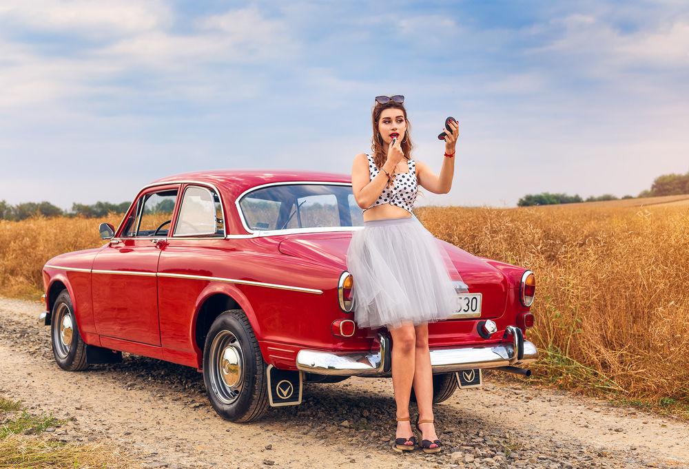 Обои для рабочего стола Девушка стоит на дороге у авто и приводит себя в порядок. Фотограф Michal Orzech
