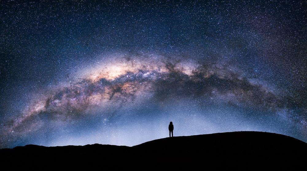 Обои для рабочего стола Силуэт мужчины, стоящего на фоне ночного неба и млечного пути