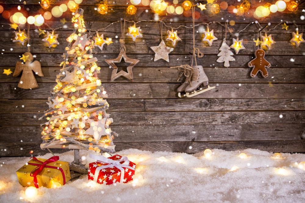 Обои для рабочего стола Новогодняя елочка стоит на снегу у деревянной стены с коньками, гирляндой и игрушками