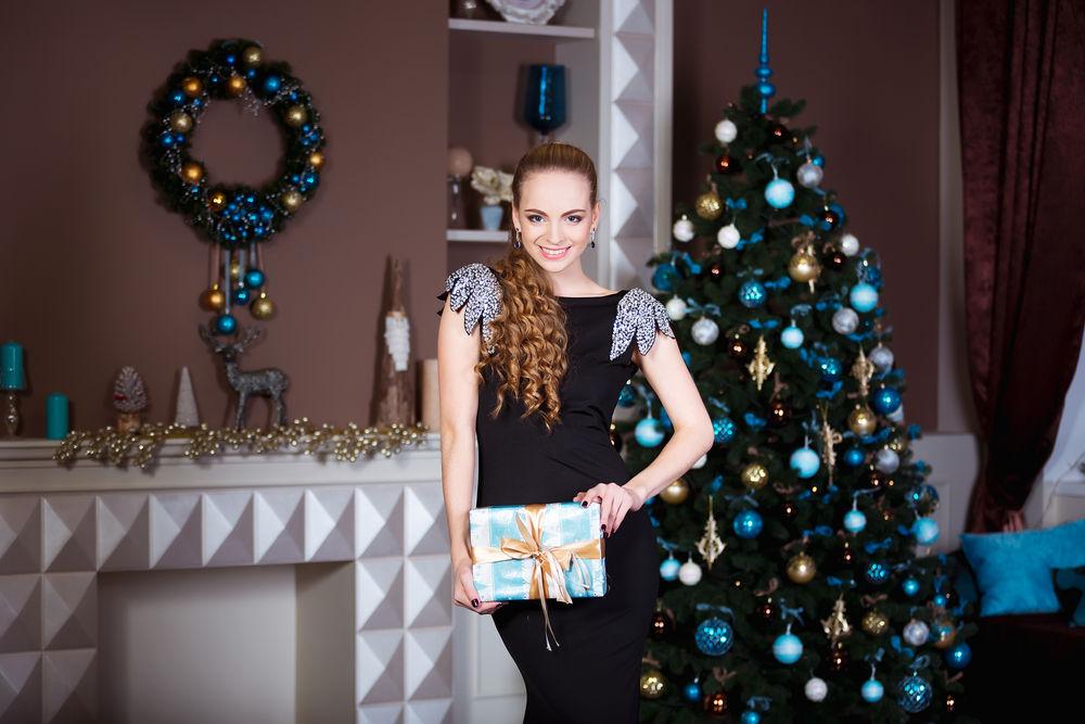 Обои для рабочего стола Девушка в черном платье с подарком стоит у елки