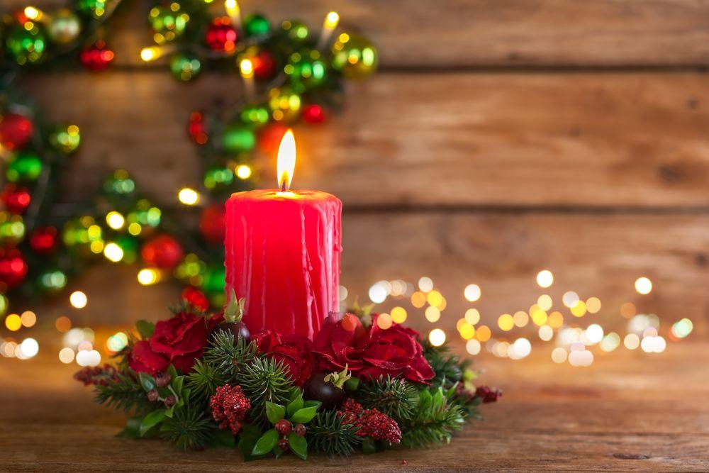 Обои для рабочего стола Горящая красная свеча в венке из еловых веток и шишек на деревянной поверхности