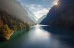 Обои Яркое солнце светит из-за гор над озером, by Andrew Bazanov