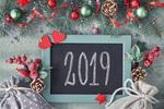 Обои Рамка с цифрами 2019 лежит на полу с веточками ели, ягод, шишек и игрушек