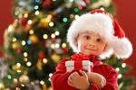 Обои Малыш с подарком у новогодней елки