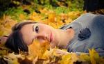 Обои Девушка лежит в осенней листве