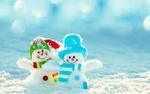 Обои Две маленькие игрушки снеговиков стоят в снегу