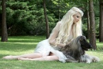Обои Модель Maria Amanda с собакой породы афганская борзая сидит на траве. Фотограф Helle Gry