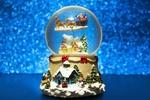 Обои Стеклянный снежный шар с рождественской тематикой внутри стоит на столе