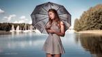 Обои Симпатичная девушка с зонтиком в коротком полосатом платье позирует, стоя на фоне природы и водоема. Фото by Icona Pictura