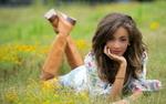 Обои Девушка в платье и сапогах лежит на лужайке с цветами