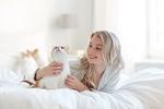 Обои Девушка в халате на постели с кошкой