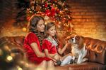Обои Две сестры в красных платьях сидят с собачкой на кожаном диване в комнате на фоне украшенной новогодней елки, фотограф Yaroslava Gromova