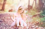 Обои Блондинка в платье сидит на опавшей листве