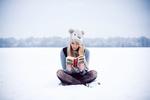 Обои Девушка читает книгу, сидя на снегу