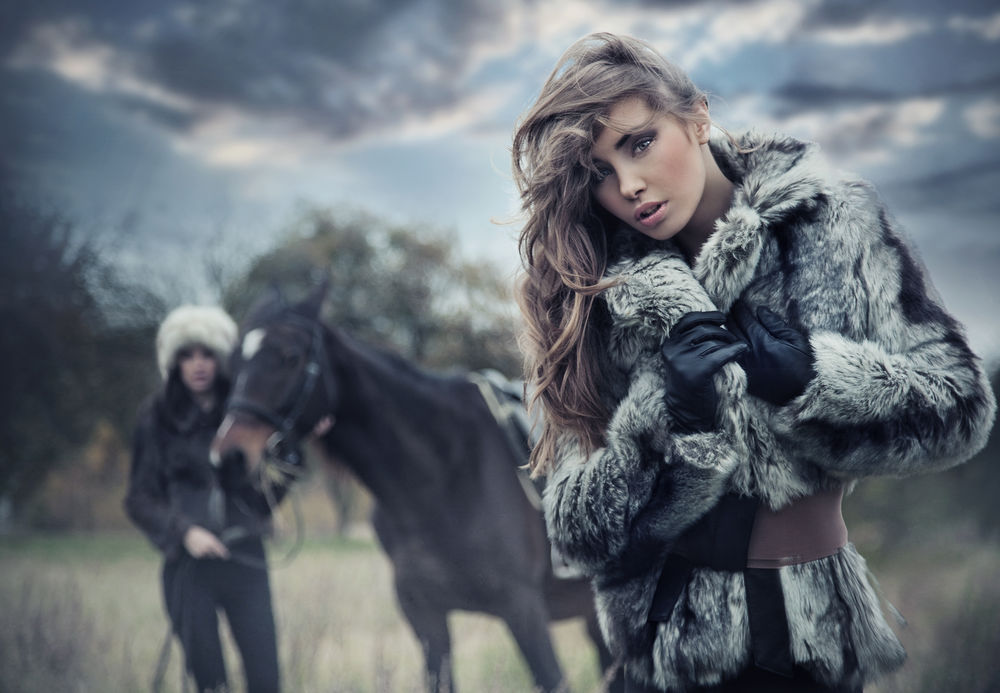 Обои для рабочего стола Девушка в шубе на фоне лошади