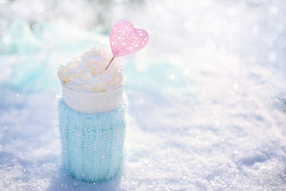 Обои для рабочего стола Стакан со взбитыми сливками, украшенными сердечком на палочке, стоит на снегу