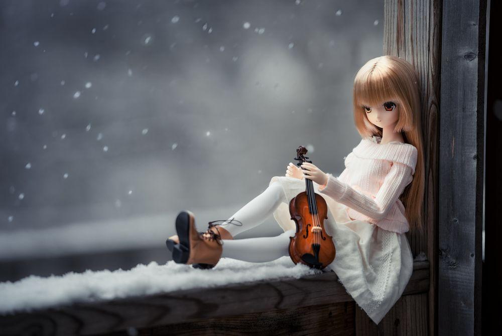 Обои для рабочего стола Куколка со скрипкой в руке сидит на заснеженном подоконнике