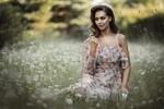 Обои Симпатичная девушка в платье в цветочек и с книгой в руке позирует, сидя на ромашковом поле