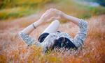 Обои Девушка лежит на траве, показывая жестом сердечко