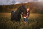 Обои Девушка в клечатой рубаке и в джинсовых шортах позирует, стоя с лошадью в поле с высокой травой. Фотограф Леонид Маркачев