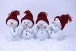 Обои Четыре игрушечных снеговичка в шапочках на сером фоне