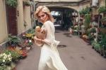 Обои Модель Оксана Стрельцова в белом платье и пакетом с продуктами позирует на улице с цветами, фотограф Roma R