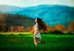 Обои Девушка бежит по полю с распущенными волосами