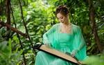 Обои Симпатичная азиатка в легком платье с музыкальным инстументом на коленях позирует, сидя на фоне природы