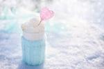 Обои Стакан со взбитыми сливками, украшенными сердечком на палочке, стоит на снегу